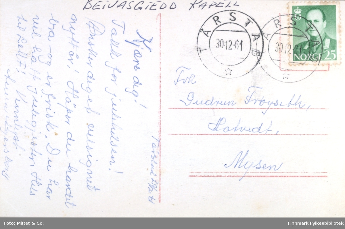 Et postkort fra Karasjok, Finnmark. På bildet kan man se flere samer og rein. På bakken ligger det sleder og i bakgrunnen kan man se en kirke. På baksiden av kortet står det skrevet at det er Beivasgiedd kapell. Postkortet datert til 1961.