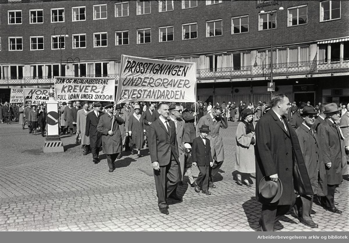 1. mai 1964 i Oslo.Demonstrasjonstoget ved Rådhusplassen.Parole: Prisstigningen undergraver levestandarden.Parole: Jern- og Metallarbeiderne krever! Full lønn under sykdom