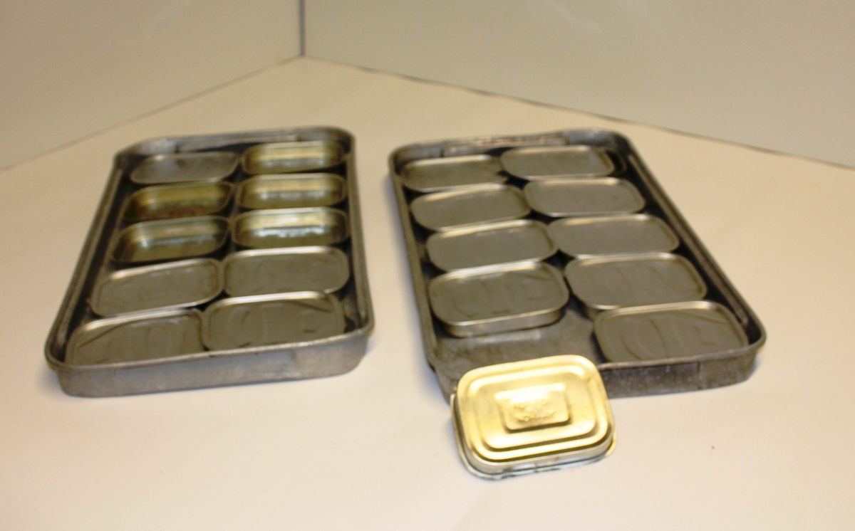 To stk. aluminiumsbrett med 10 stk sardinbokser i kvar og lause lok.