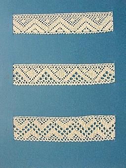 Blått kartongark med tre prover knypplad skånsk spets från östra Göinge härad. Vid varje prov står en stor bokstav. A. 13x 2,7 cm B. 13 x 2,6 cm C. 13 x 3,2 cm