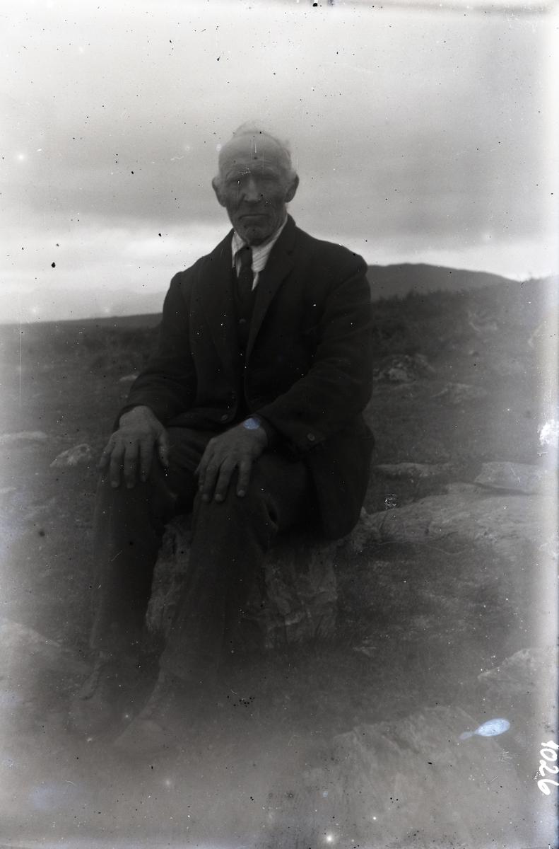 Bildet viser en dresskledd mann som sitter på en stein på fjellet. Han har lys skjorte og slips, og har klokke på armen.