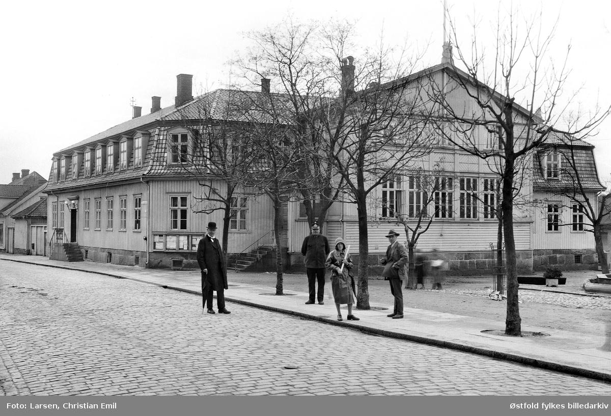Gateparti fra Sarpsborg, Domhuset ved Sarpsborg torv, i forgrunnen ei gruppe på fire ukjente personer, politimann og to menn, samt kvinne med regnkåpe.