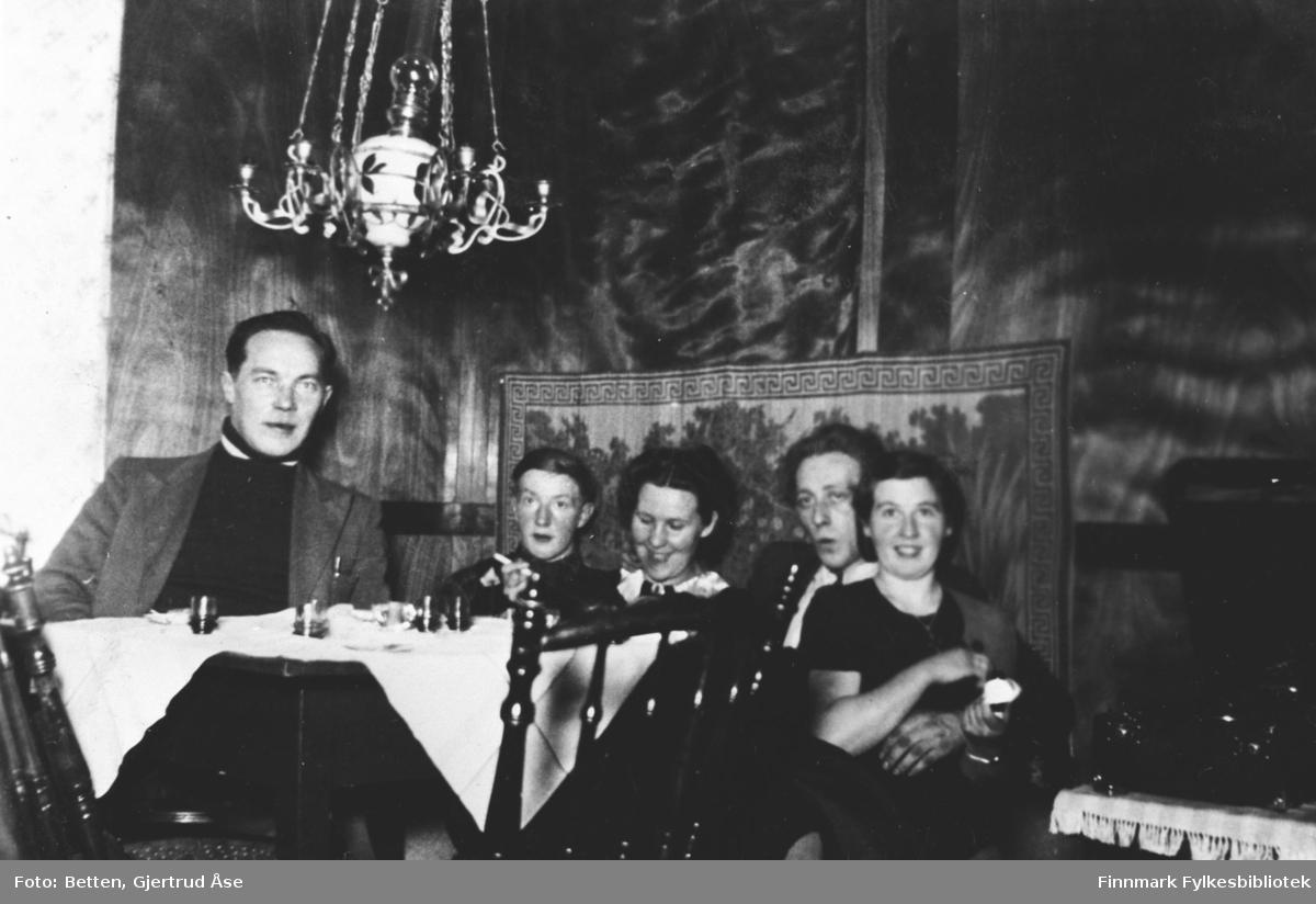 To kvinner og tre menn sitter i stua på hytta hos Ingeborg. Fra venstre: Abraham Mikkelsen, Nils Betten, Ingeborg Moan, Otto Pleym og Gjerdrud Betten. Det henger en oljelampe over bordet, bordet er dekt med en hvit duk. På bordet står det små likørglasser men noe oppi.  Under bildet på albumet står det ' I kosekroken hos Ingeborg'.