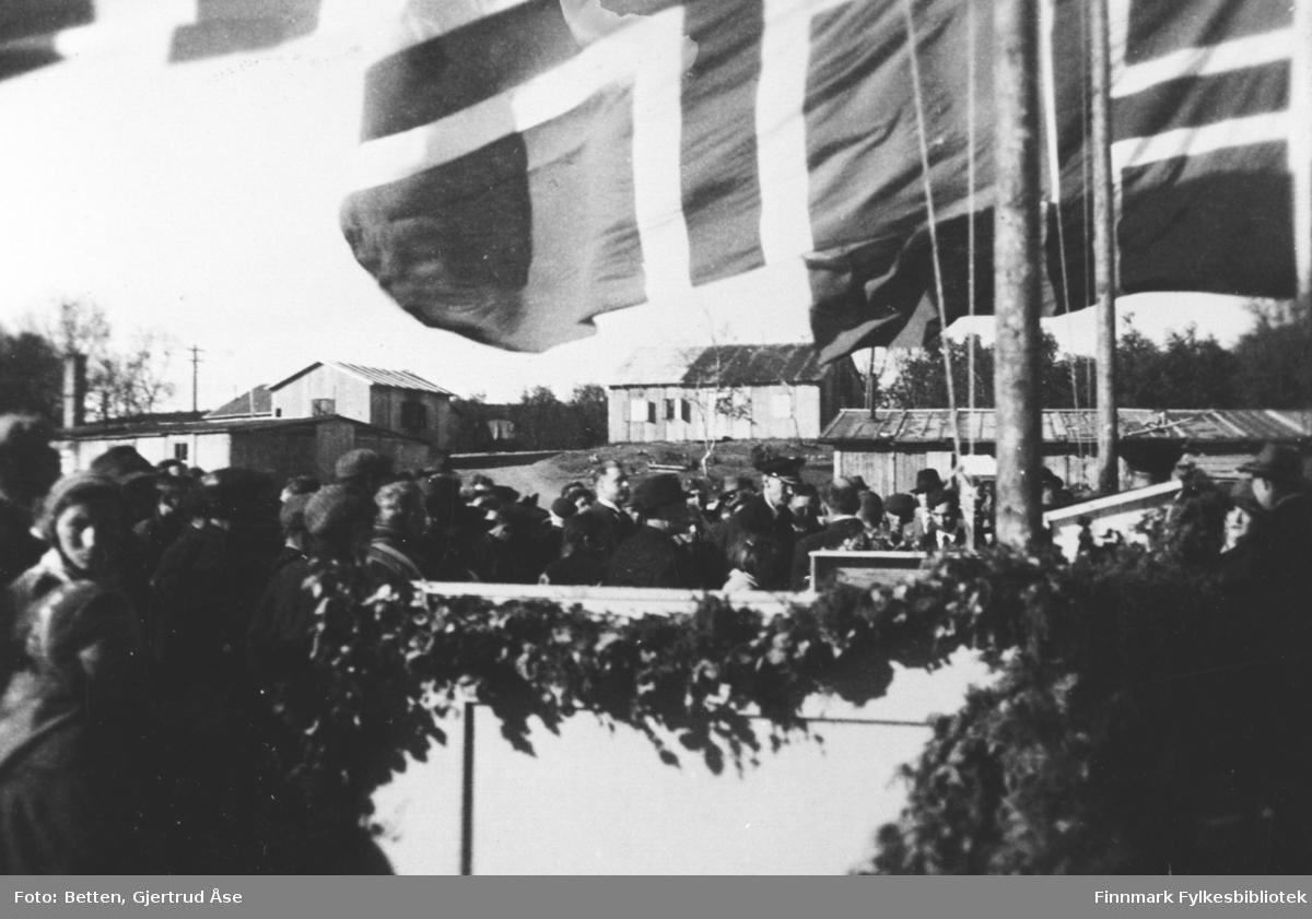 Kong Haakon VII på besøk på Nyborgmoen i juli 1946. Kongen står mitt i folkemengden.  Flaggene er heist opp og inngangen til byggningen er pyntet med kranser.