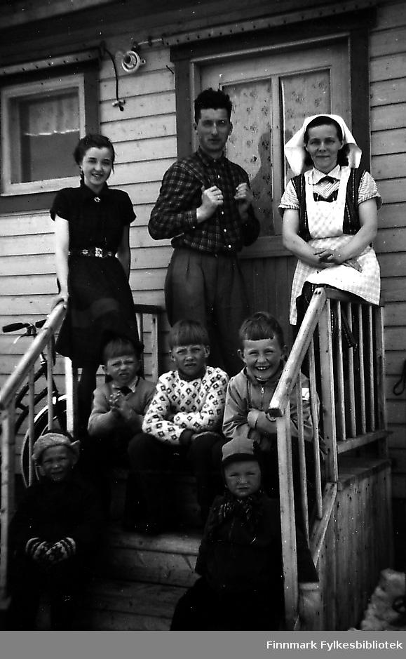Familien Albert og Anna Andersen fotografert på trappa. Moren Anna sitter på rekkverket kledd i kjøkkenassistentklær, på andre side av trappa sitter datteren Rigmor, faren Albert står mellom dem. Fem gutter sitter på trappa foran dem, alle smiler. Barna fra venstre: Knut Andersen, hannes bror Rolf og Bjørn Ottar Betten. De to guttene på nederste trappe er ukjente.