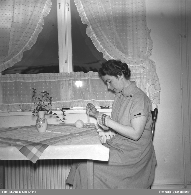Jenny Drannem sitter på kjøkkenet og stopper en sokk. Bildet er tatt i leiligheten der familien bodde i Tollboden i Hammerfest