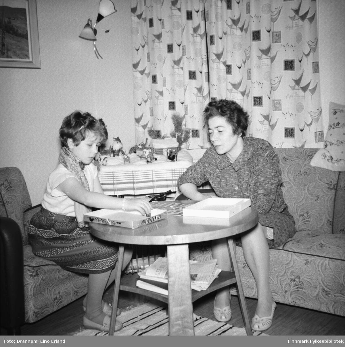 Turid Lillian og Jenny Drannem spiller et brettspill ved bordet i stua deres i Tollboden