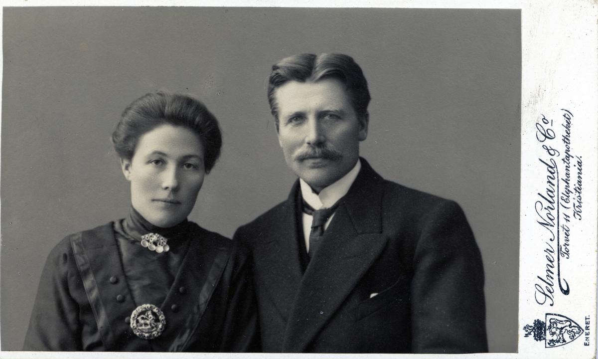 Kvinne og mann avbildet i halvfigur. Hun er kedd i mørk kjole/bluse med sølje i hasen og på brystet. Han har mørk jakke/dress, hvit skjorte og slips