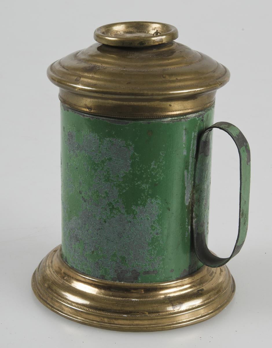 Vaxljusstake av grönmålad plåt. Överdel och fot av mässing. Vridbart lock med hål. Invändigt blåmålad.