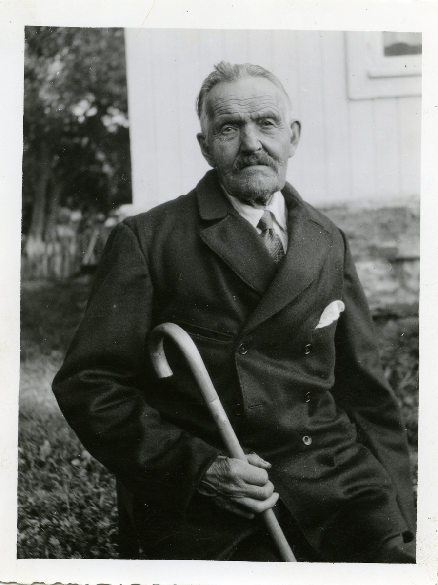 Portrett av en eldre mann sittende med en spaserstokk i hånda. Mannen er iført dress og skjorte med slips.