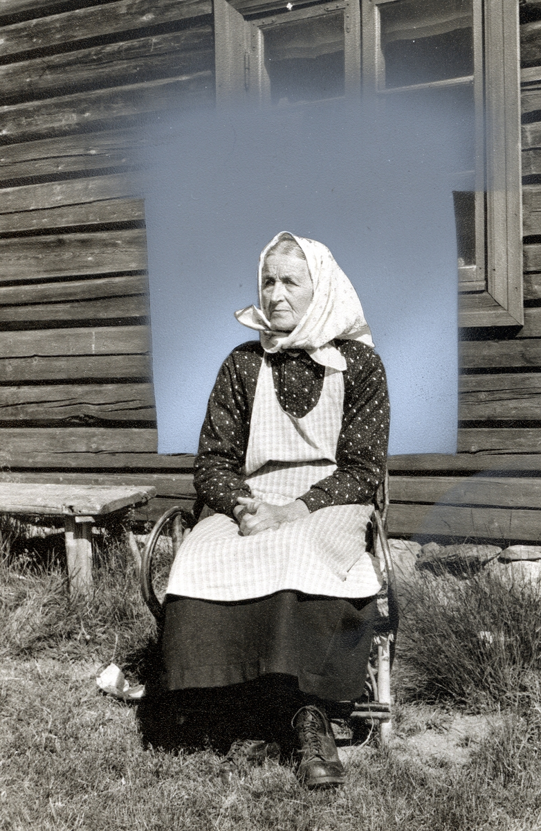 Kvinne som sitter utenfor vinduet i en tømmerbygning. Hun er kledd i bluse med lyst mønster, svart skjørt, rutete forkle og hun har skaut på hodet.