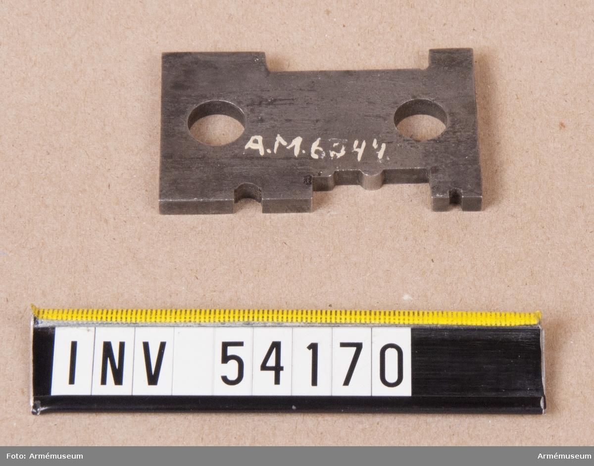 Grupp E VIII.  Ingår i en sats instrument för besiktning av 10,15 mm  kammarskjutningsgevär m/1884. Satsen omfattar schampluner för hane, slutstycke, avtryckare,  släptång, lådans yttre och inre dimensioner, svansjärn och  patronläge samt gängtapp, bajonetttolk, kalibertolkar,  brillor,mynningshylsa, sikte, tolk till sikte och siktskåra, 28  tolkar till besiktning, sifferstansar, borrstål och div. verktyg.