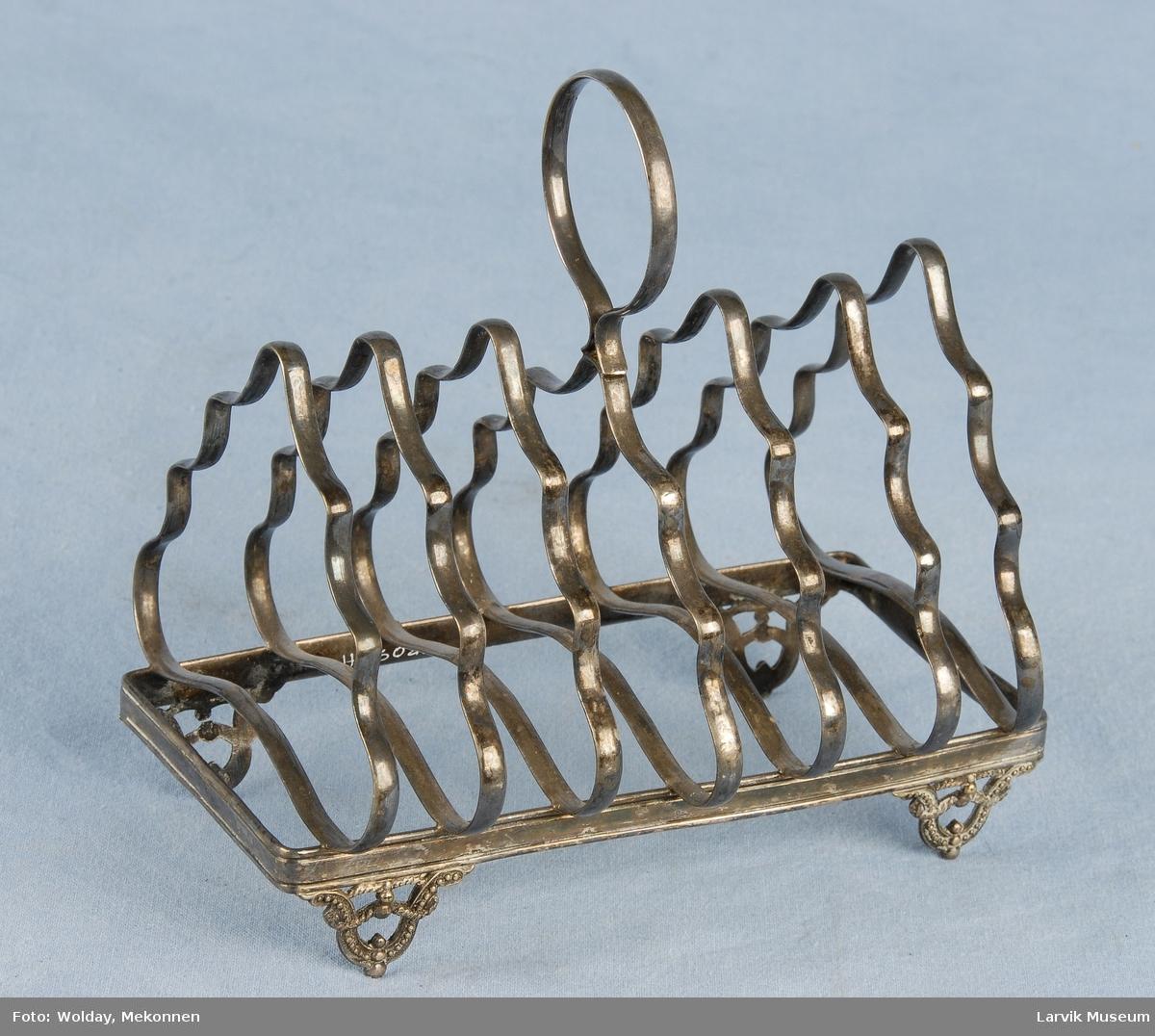 Form: Fire små føtter med dekor, holder en rekatngulær ramme oppe. Til denne rammen er festet syv bølgete trekanter. På den i midten er det festet et håndtak.