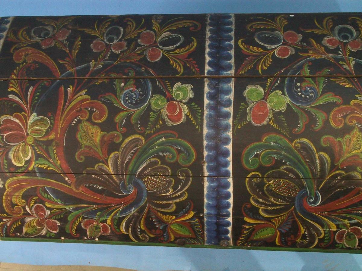På lokk og  front to  motiver:   ranke  i rødbrunt med blad og   blomster  i  dypblått.  rødbrunt. gult og grønt. på sort bunn. Nøkkelhull med  merker etter hjerteformet beslag. sok er borte.