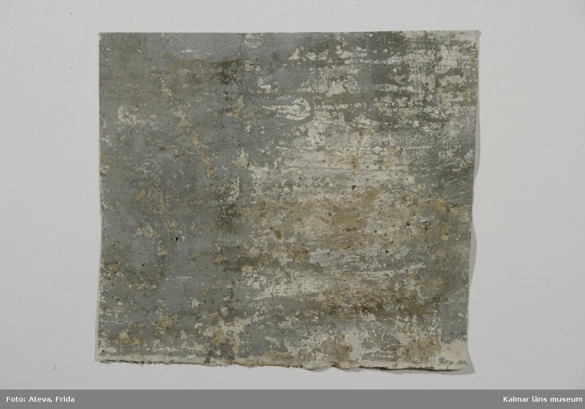 KLM 39224:9. Tapet av papper. Tapetens mönster är borta men botten är målad i ljust grå färg. Datering: 1700-1800-tal.