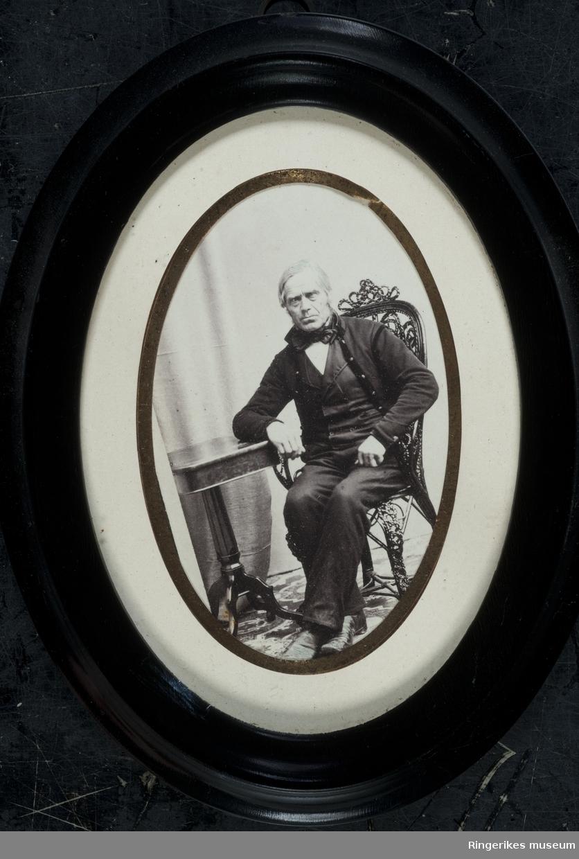 """Svart/hvitt portrett. Iflg. påskrift bakpå rammen er bildet av Jens Slevigen. En tidligere påskrift har tydeligvis hatt med årstall for fødsel og død. Nå er kun """"d. 1885"""" (eller 1883) synlig. Ellers er fotogarfiet i en oval svart ramme med off-white passpatur med gullkant ned mot fotografiet."""
