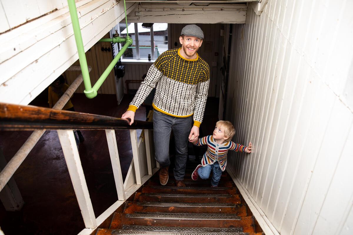 Mann og barn går opp trapp i fabrikklokale (Foto/Photo)