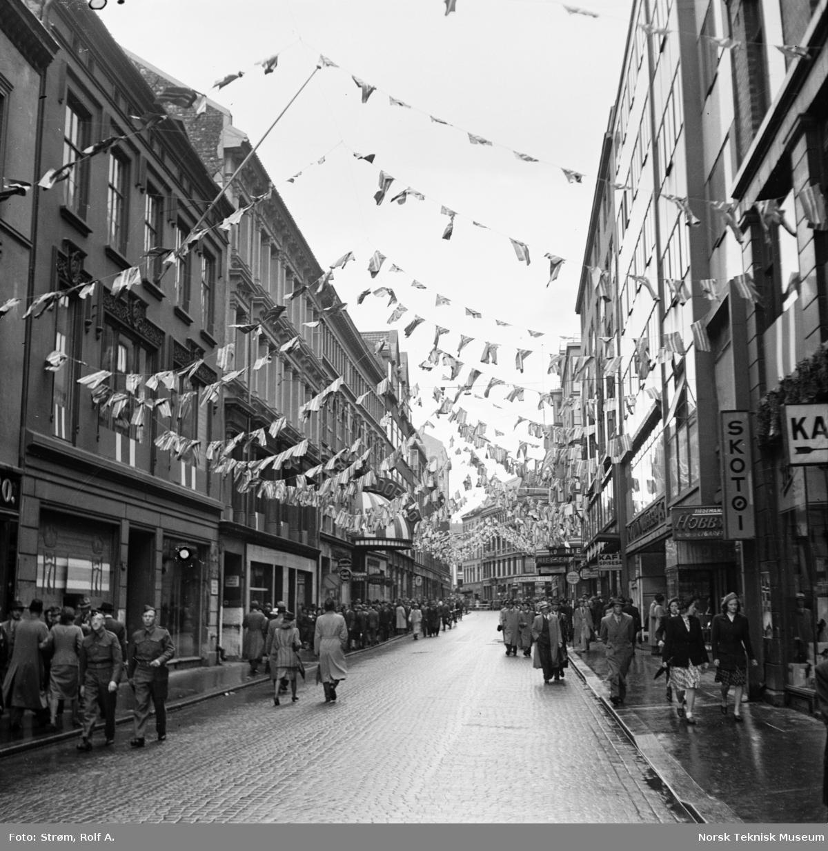 Forberedelser til kong Håkons hjemkomst, Torggata forbi Eldorado kino er pyntet med flagg og Håkon 7's monogrammer i vinduene, juni 1945.