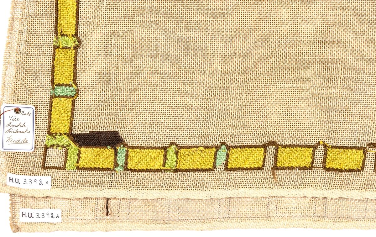 2 stycken, gles linnelärft, ej hopsydda. Avsedda till kudde.  Uppritat mönster, rutig bård runtom. Påbörjat broderi på ena stycket, petit point, lingarn, gula rutor med gulgröna fält emellan, spegeln troligen avsedd vara brun.  Pappersetikett med bläck skrivet: Till Landsh. Lubecks kudde.  En trubbig synål. s.k. stramaljnål, fastsatt i ena stycket.
