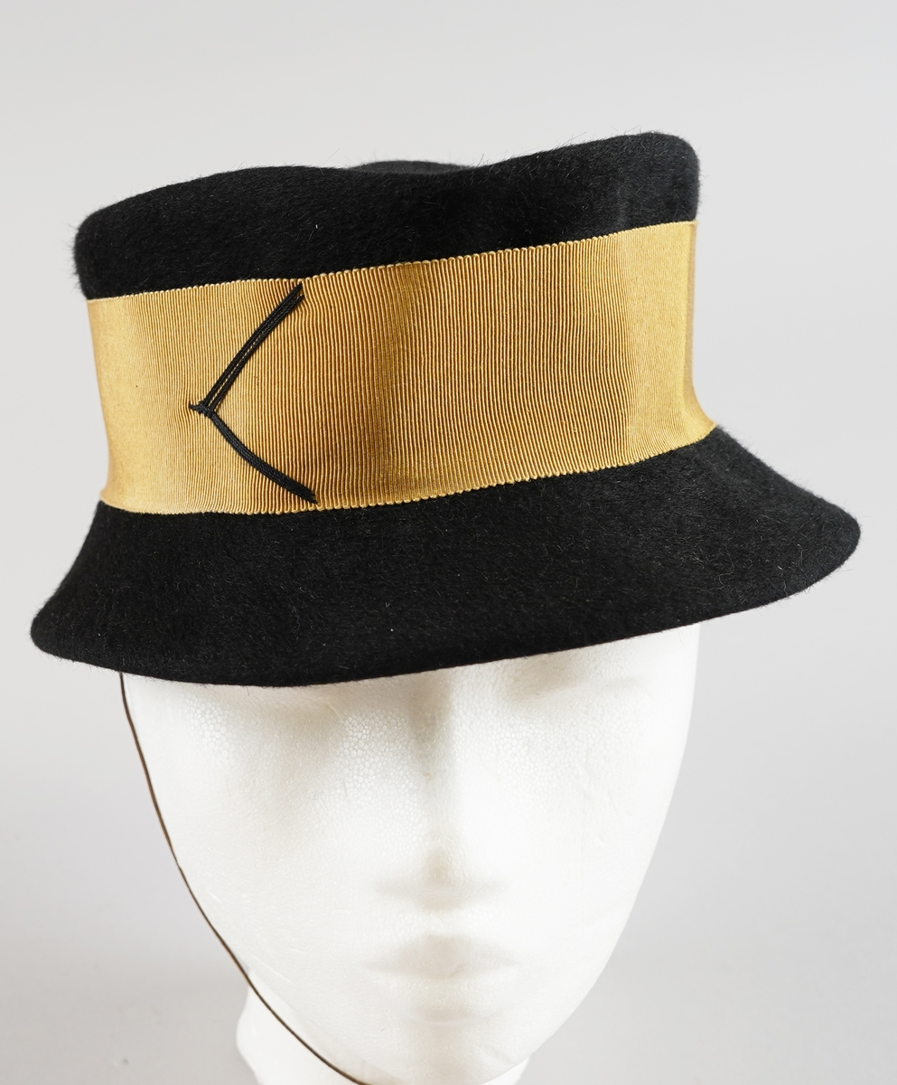 Svart hatt i ullfilt med gyllent pynte band og tynt strikk til feste.