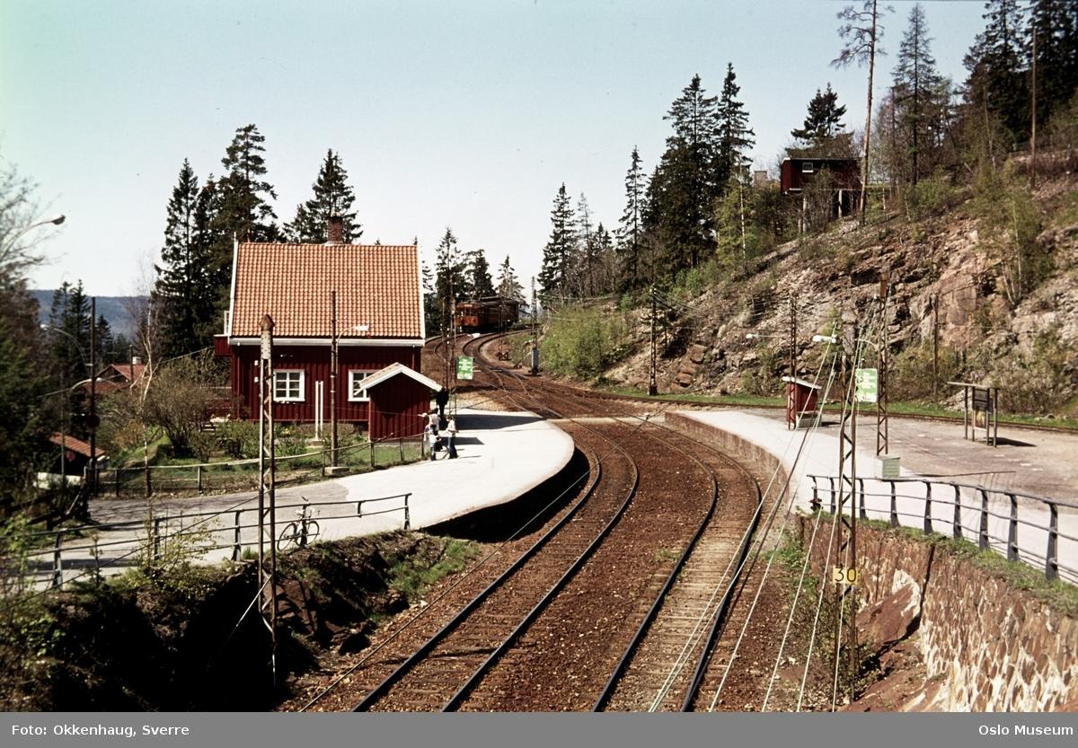 Holmenkollbanen, Holmenkollen stasjon, perrong, mennesker, hus, trikk, skog