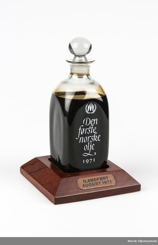 Karaffelformet flaske på sokkel. Flasken inneholder olje ilandført fra Ekofisk-feltet i august 1971. Tekst på tilhørende eske (som selgeren ikke hadde, men oljemuseet har fått bilde av denne): Inntekten av denne flasken går i sin helhet til eldreomsorgen hjemme og ute, representert ved Telefonkontakt og Flyktningerådet. De har nok heller ikke unngått stadig å bli minnet om de eldres ofte tragiske liv i ensomhet. En for Dem så selvfølgelig ting som telefon betyr for ensomme eldre en mulighet for kontakt med medmennesker. Telefonkontakt er en nyopprettet organisasjon som arbeider intenst for å skaffe eldre mennesker telefon. Vi tror De vil være enig i at formålet er den første Nordsjø-oljen verdig.