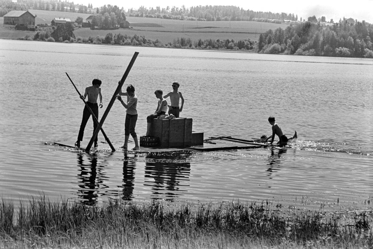Svart-hvitt bilde av fem ungdommer i shorts som seiler på en hjemmelaget flåte. (Foto/Photo)