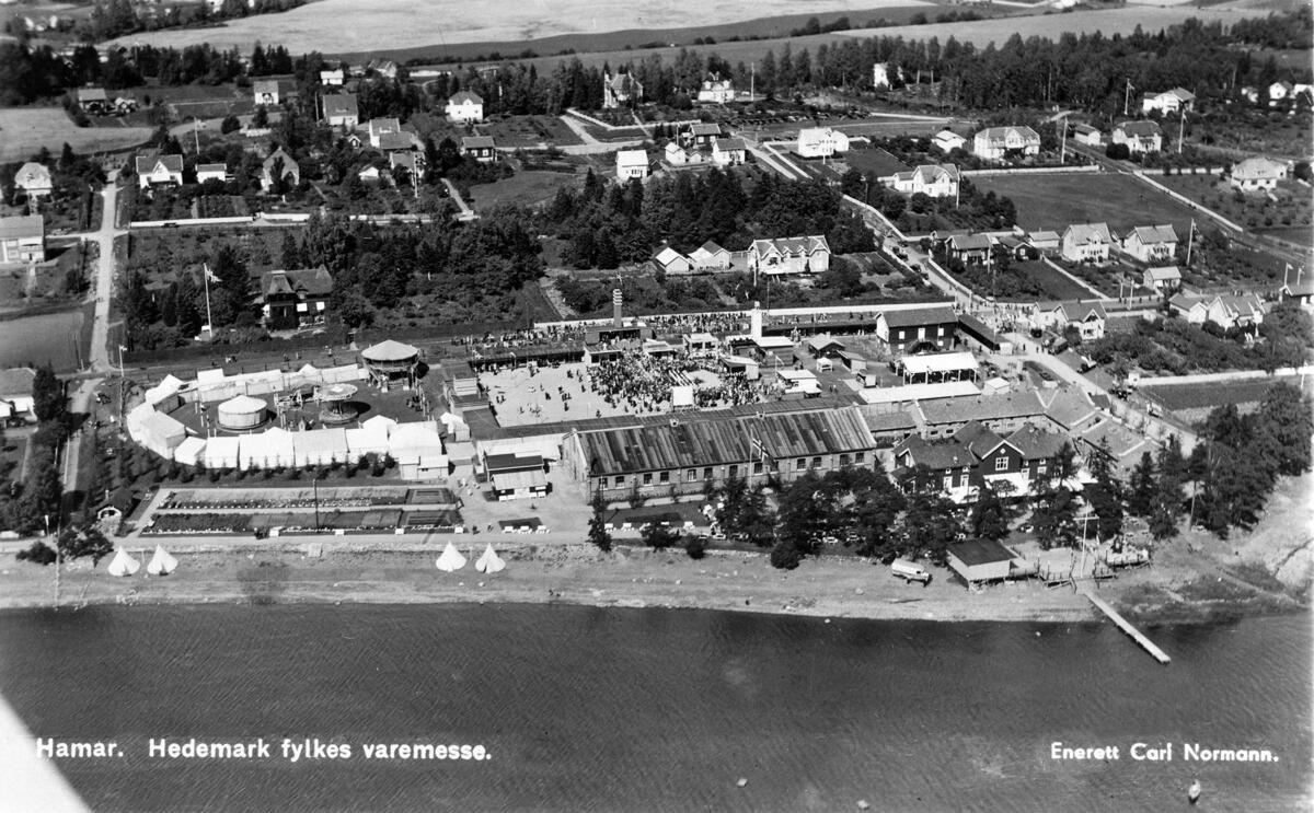 Flyfoto som viser tivolitelt til venstre og en stor plass med utstillingsboder samt Ridehuset på Hamar og omliggende villabebyggelse. Mjøsa i forkant. (Foto/Photo)