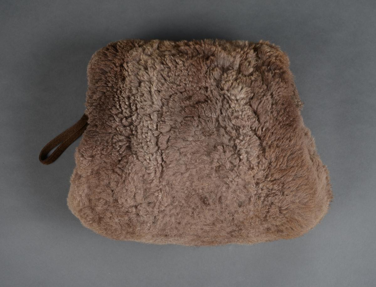 Muffe med gråbrun pels og gråbeige silkefor. I den ene enden er det en hempe til å henge den opp etter.