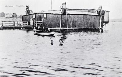 Badehus fra 1885, beliggende i Mjøsa utenfor Storhamarstranda i Hamar.  Huset ser ut som en lav brakke som flyter på tønner i vannet. (Foto/Photo)