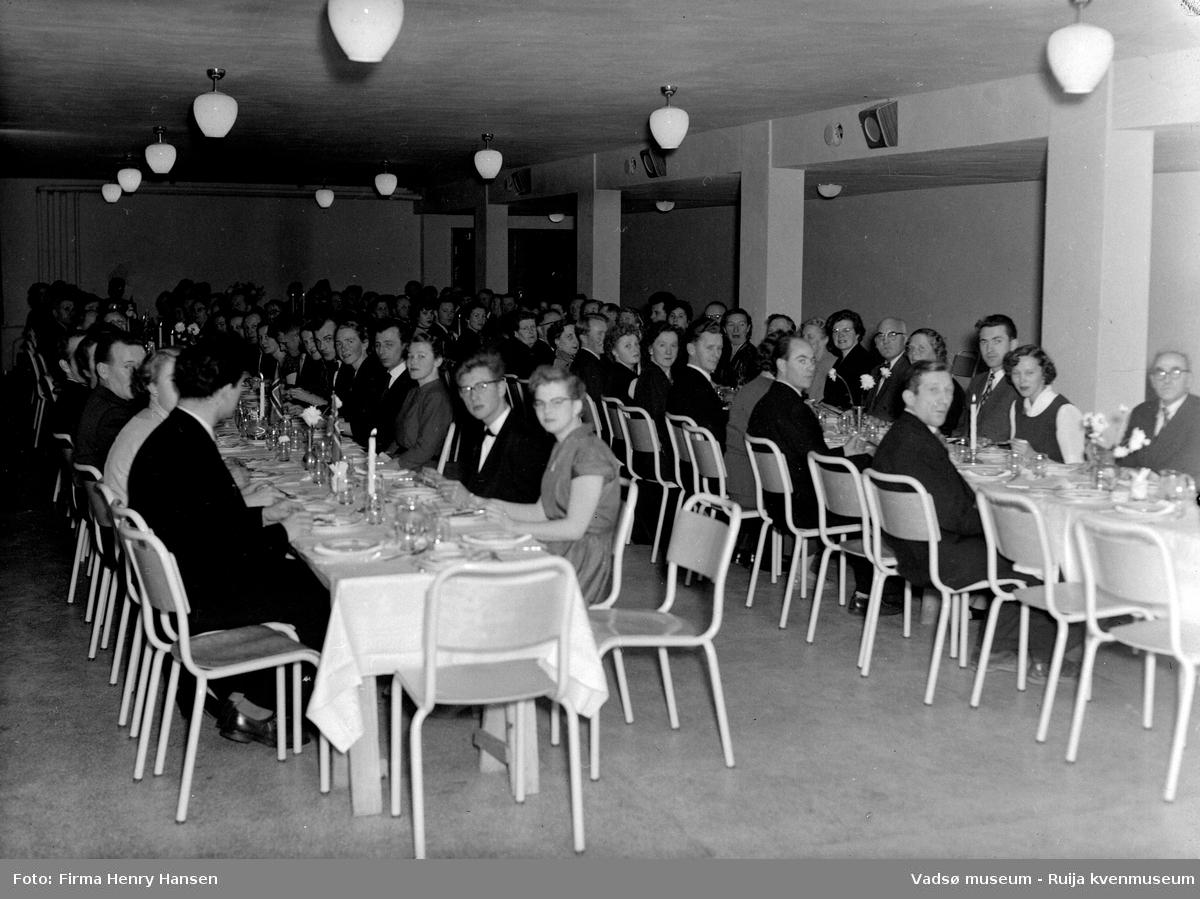 Gruppebilde på Vadsø folkeskole, festmiddag.  Bildet er trolig tatt ved innvielsesfesten for Vadsø folke- og framhaldsskole 28.10.1956. Kilde: Melding om Vadsø folke- og framhaldsskole for skoleårene 1951/52-1959/1960. Vadsø 1962.