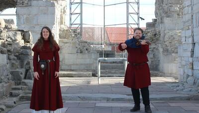 Syngende guider: Middelalderkledd ungdom, ei jente til venstre og en gutt med fele til høyre, inne i Hamardomen (vernebygget over domkirkeruinen).. Foto/Photo