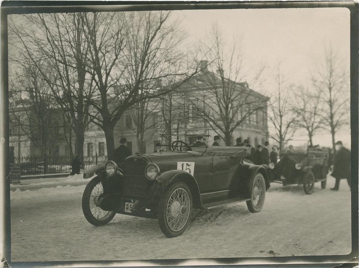 Bil under en biltävling med människor i bakgrunden. Fotografi från John Neréns motorhistoriska samling.
