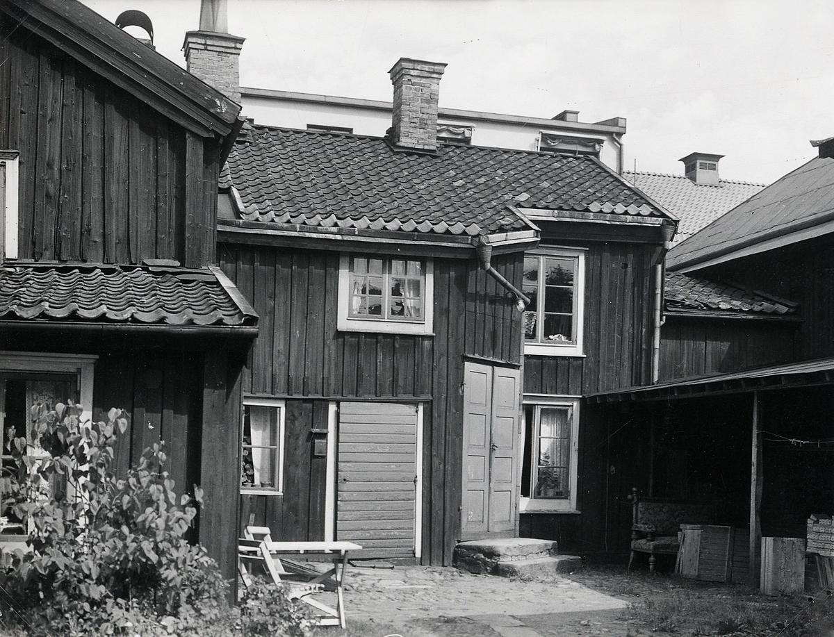 """""""Båtsmansbacken"""", baksidan av """"Snus-Lundgrens"""" fastighet, kv. Håkan Sjögren nr 3.   """"Snus-Lundgren"""" - Erland Petersson Lundgren (1834-1922), handlande, kv. Håkan Sjögren 3, Växjö. F. i Åseda. Gift med Kristina Ohlsson (1827-1905).  (Källa: Folkräkning 1890 och 1900, Växjö stad, Riksarkivet. Sveriges Dödbok 1860-2017)"""
