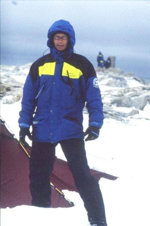 Porträtt av en man med glasögon, i polarforskningssekretariatets klädsel. Han står vid ett tält vid Andréelägret på Vitön med huvan uppfälld, det blåser och är kallt.