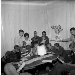 En samling med männiksor sitter runt ett bord och sjunger ti