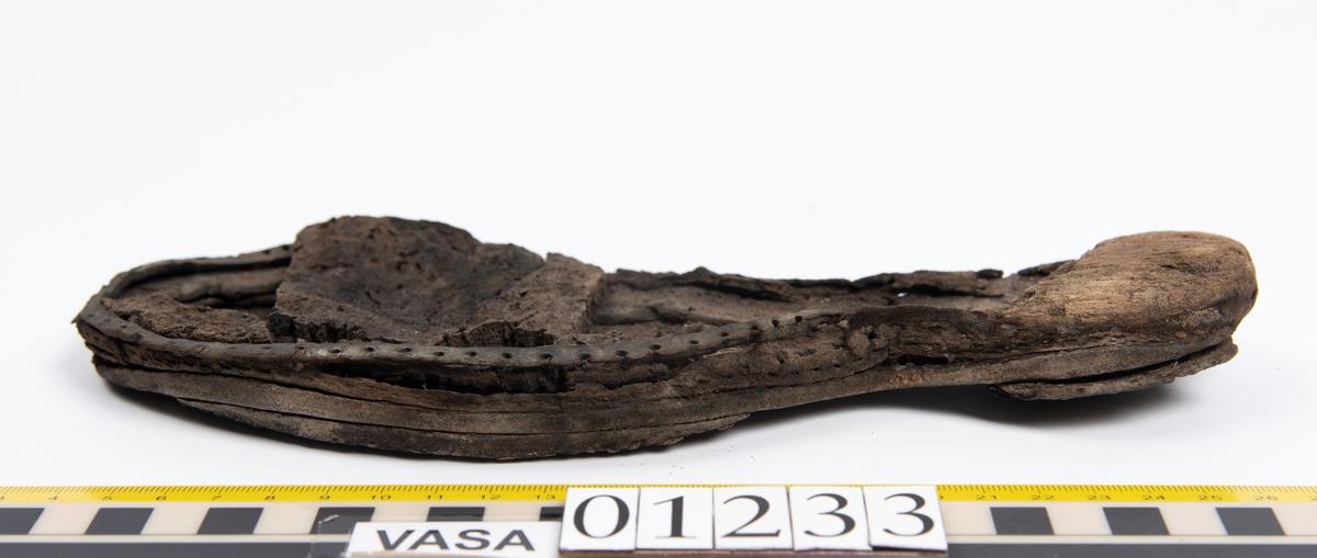 Del av sko; skobotten samt bakkappa. Bottnen består av yttersula med träklack, korksula och holtrand och härrör troligtvis från en vänstersko. Träklacken är sprucken och något fuktig. Träklacken, holtranden och korksulan sitter fastpliggade vid yttersulan. På undersidan, dels vid klackpartiet och dels vid tåpartiet, finns två fastpliggade laglappar. Lädret är mycket kraftigt och välbevarat.