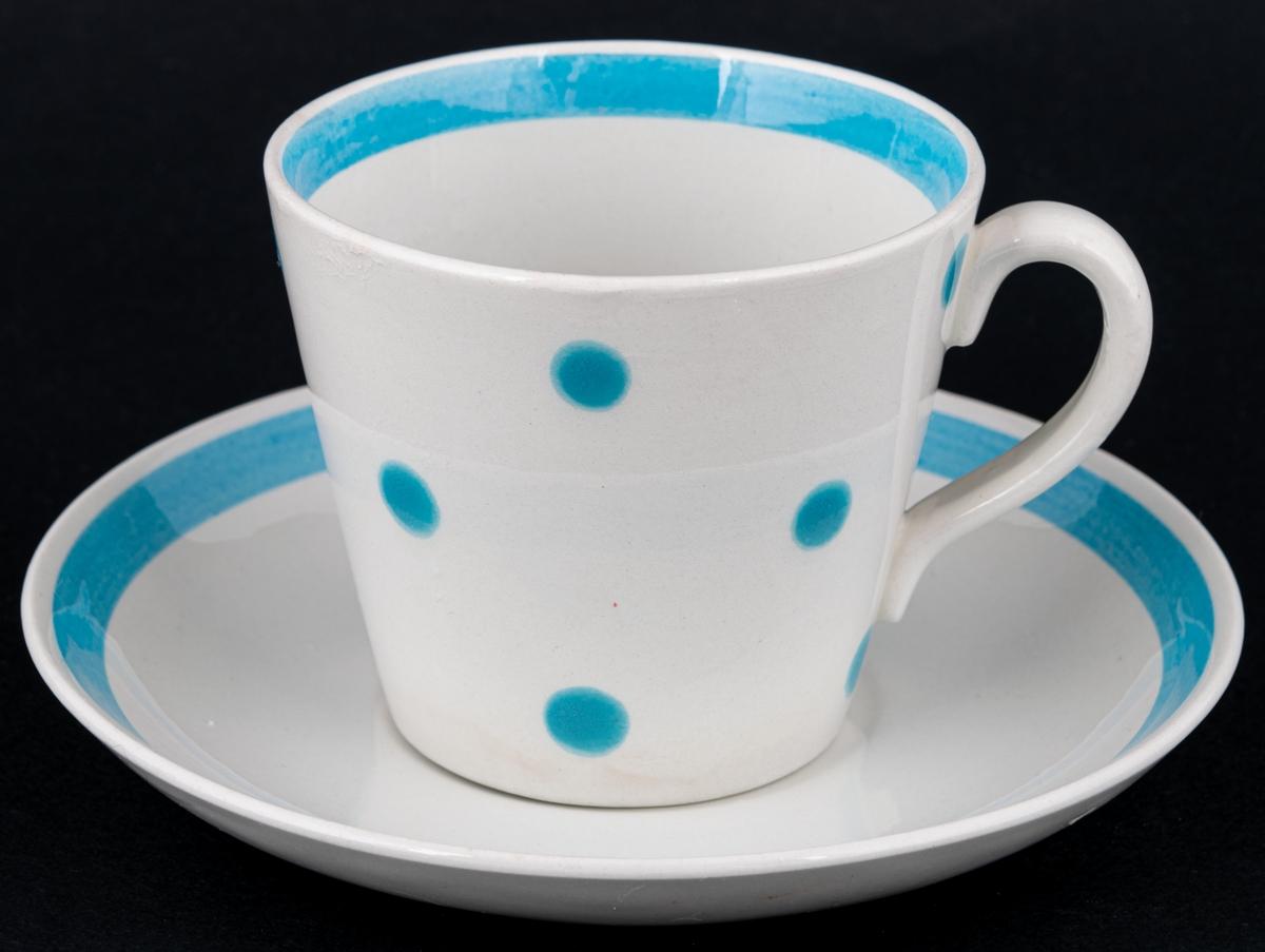 Kaffegods i flintgods, modell AU, dekor Dalarö från 1957 ritad av Eugen Trost; turkosa glest spridda prickar på koppen, turkos rand på fatets kant.