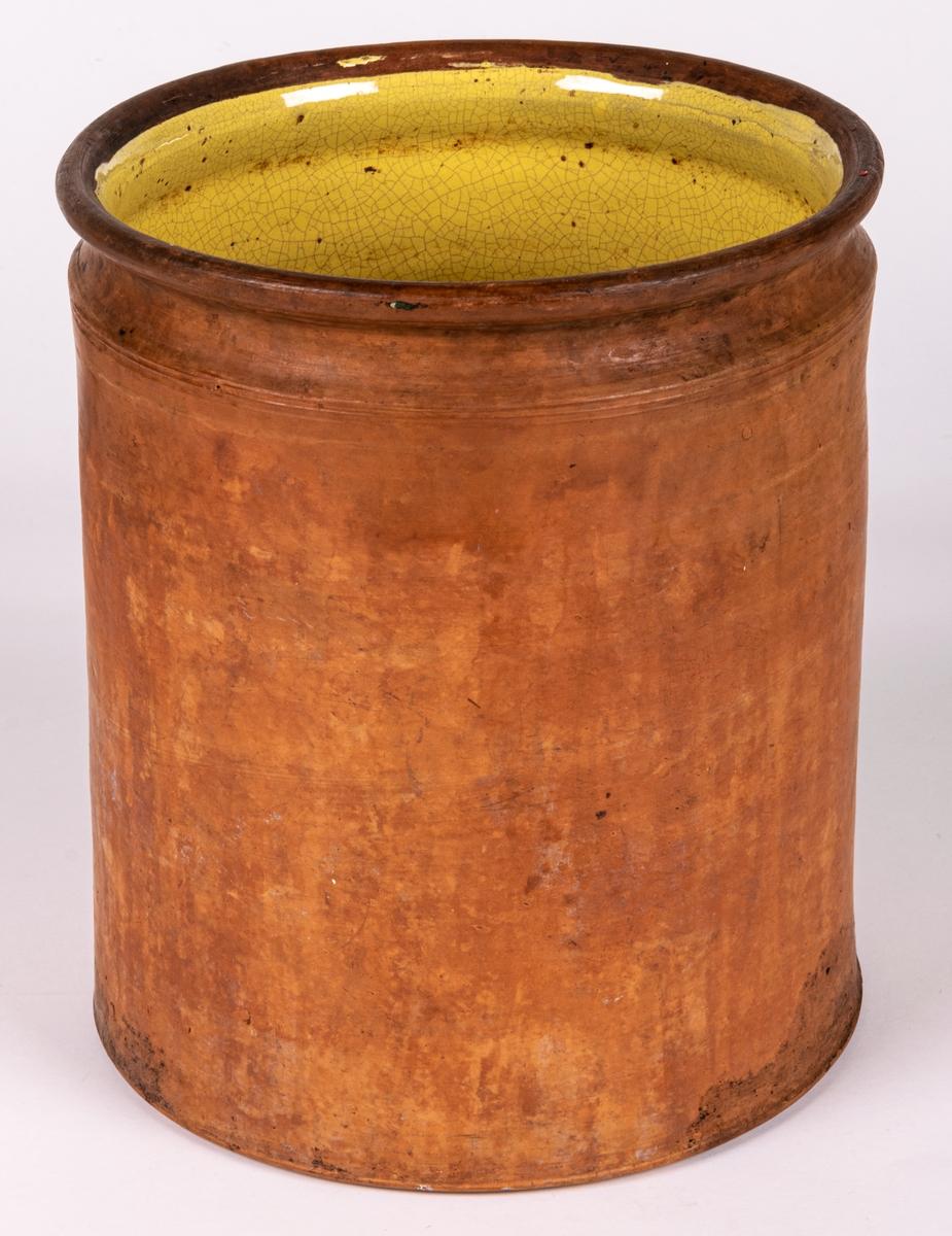 Halvglaserad rak kruka av bränd lergods, insvängd profil upptill, gul glasyr på insidan, oglaserad yttersida. Storlek 6 liter. Användes till förvaring av mat.