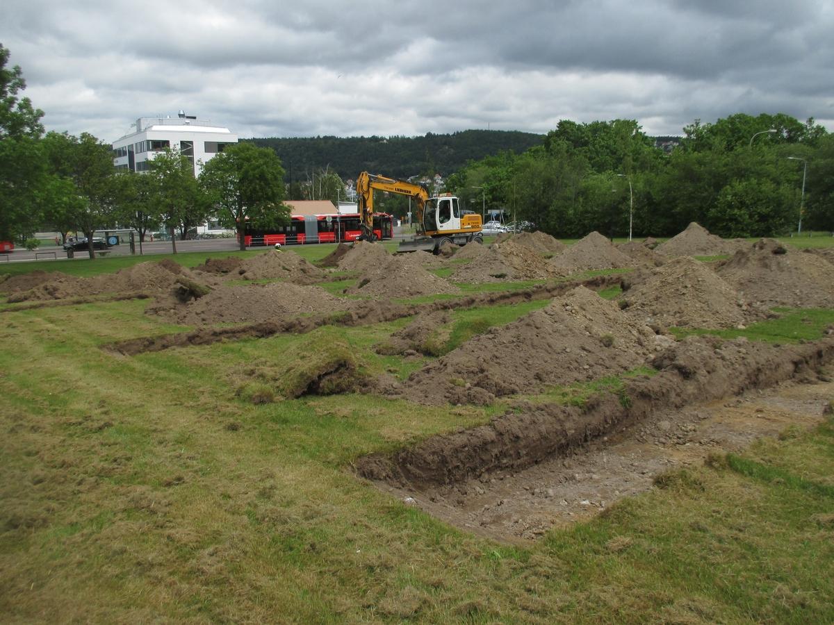 Sökschaktgrävning med grävmaskin i den södra delen av förundersökningsområdet vid Sandagymnasiet. I bakgrunden ses Engelska skolan.