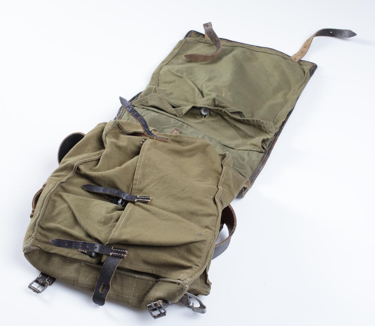 """Tysk M39 ryggsäck med en förslutningsklaff av hästpäls som täcker hela framstycket. Alla spännen och knappar är i målad stål. Ryggsäcken i övrigt är tillverkad i grön kanvass. Bärremmar och förslutningsremmar är i svart läder. Upptill på baksidan är märkt """"Wittkop & Co Bielefeld 1942"""". Bärremmarnas insida är stämplade med stämpel. Under locket finns märkt """"Ob. Gefr. + otydligt namn"""". (Obergefreiter + namn)."""