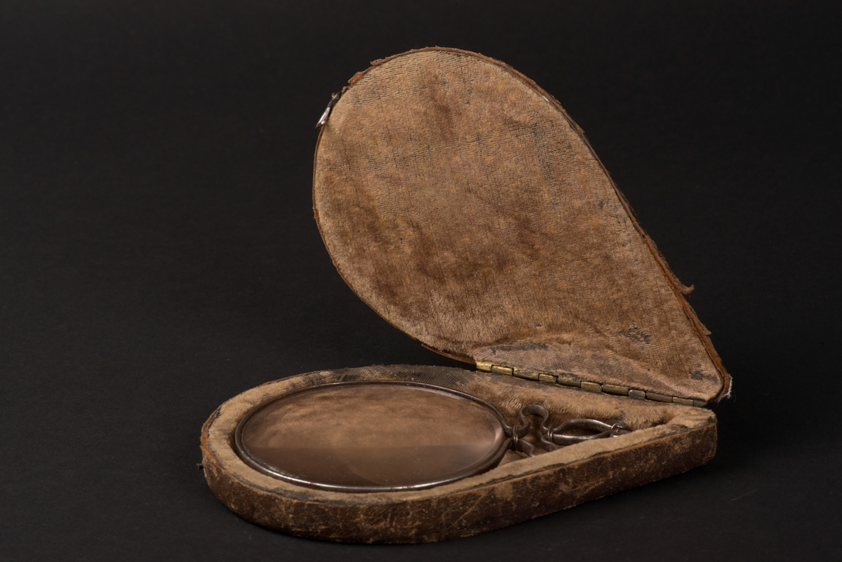 Förstoringsglas i fodral.  Förstoringsglas med båge och kort handtag/hänkel av järn.  Skinnklätt fodral. Inuti fodrat med brun sammet.  Rest av klisteretikett på förstoringsglaset.