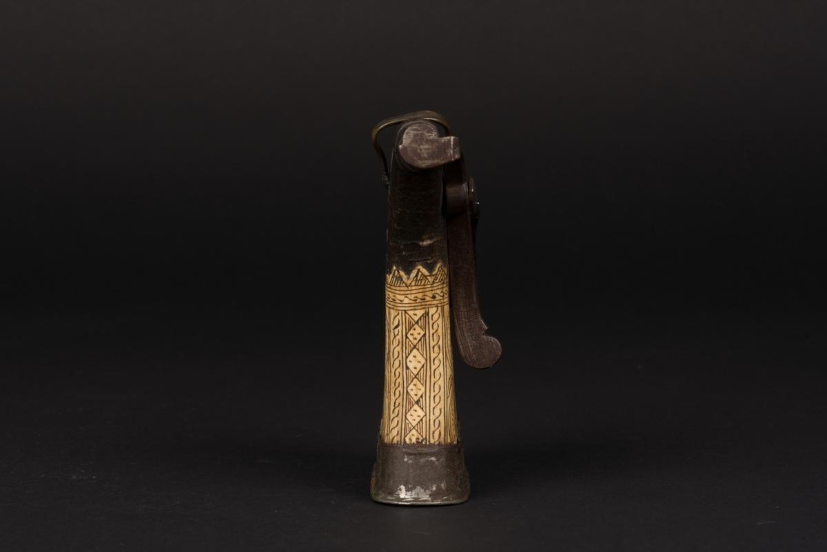 Kruthorn av horn. Stomme av kreaturshorn som är överdraget med ett skikt av ben som dekorerats med växtornament. Botten och mynningen är av järn. Fjäderbelastad påfyllningsanordning. Ögla av mässing.