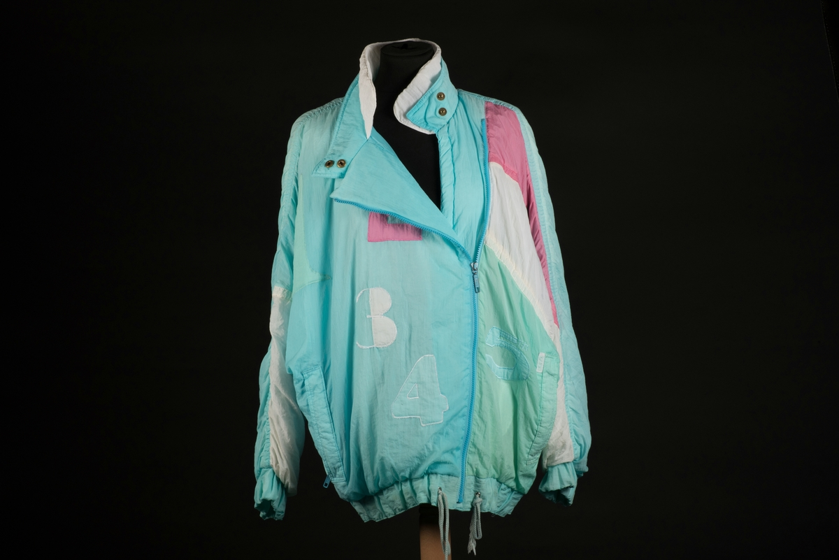 Skidjacka i pingvinmodell tillverkad av syntetmaterial, nylon/polyester. Jackan i turkost, rosa, mintgrönt och vitt är sydd i så kallade pingvinmodell. Mönstret består av oregelbundna fält med de olika färgerna. På framsidan finns ditsydda applikationer med siffrorna 1 till 5 i olika färger. Den ljusblå dragkedjan är placerad något till vänster och diagonalt på framsidan. Den upprättstående kragen är försedd med två tryckknappar, och innanför finns ytterligare en krage. Det finns två fickor, försedda med dragkedjor. Jackan har insydda resårer nedtill samt i ärmsluten. Nedtill finns det även en dragsko med snodd.