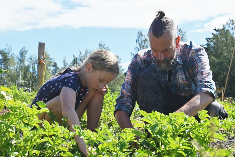 Ung jente og voksen mann sitter på huk og jobber i de grønne skolehagene. (Foto/Photo)