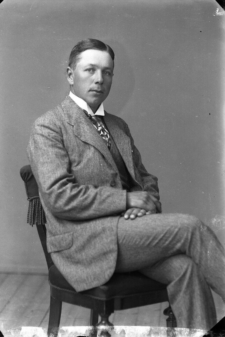Porträtt av en man som sitter på en stol.