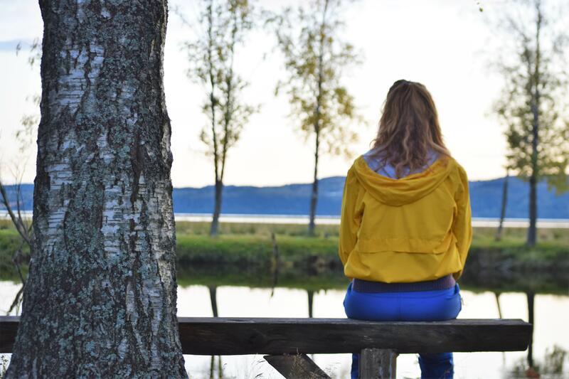 Foto av en jente som sitter på en benk og ser ut over Glomma (Foto/Photo)