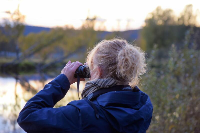 Foto av en kvinne som ser i kikkert utover Glomma (Foto/Photo)
