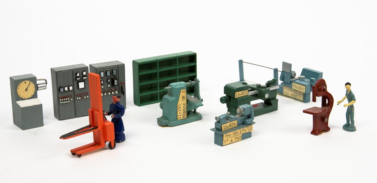 Modell verkstad, bestående av flera modeller i olika skalor föreställandes maskiner, kringutrustning, kontorsmöblemang samt figurer för verkstadsmiljö. Modellerna består av trä, plast och metall. Varav några har magneter eller klistrerremsa för fasthållning på underlag. Flertalet modeller har nummer-märkning i botten eller mindre etiketter vid sidan med typbeteckning. Medföljer två lösa etiketter.