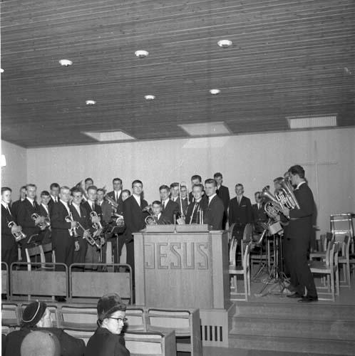 Scen med ett talarbord sett framifrån. Det står Jesus på talarbordet. En blåsorkester står på scenen snett mot publiken. De har sina instrument i händerna. Börje Andersson står som nummer tre från vänster. Vid talarstolen, som tvåa från höger står Rolf Sjöö.